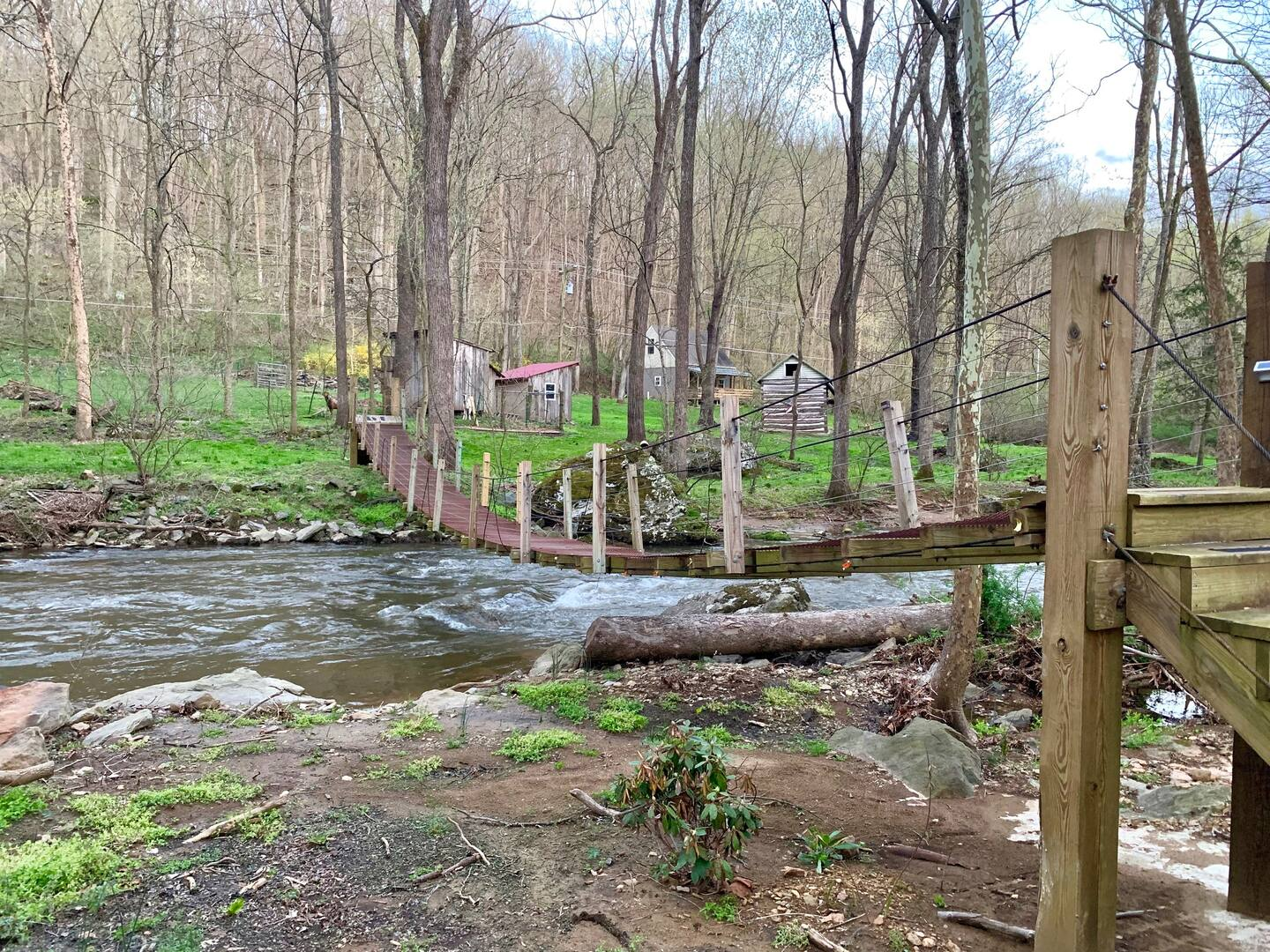 Walk Across A Suspension Bridge To Reach This Whimsical Maryland Cabin On The Creek